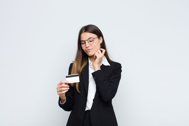 Young pretty woman smiling with a happy, confident expression with hand on chin, wondering and looking to the side with a credit card