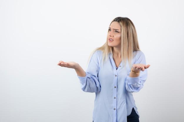 Giovane donna graziosa in piedi e litigare con qualcuno sul muro bianco.