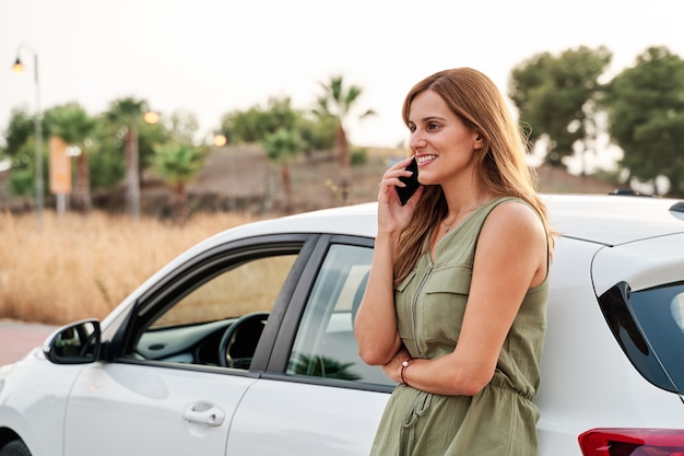 Young pretty woman standing leaning against her car while talking on her smart phone.