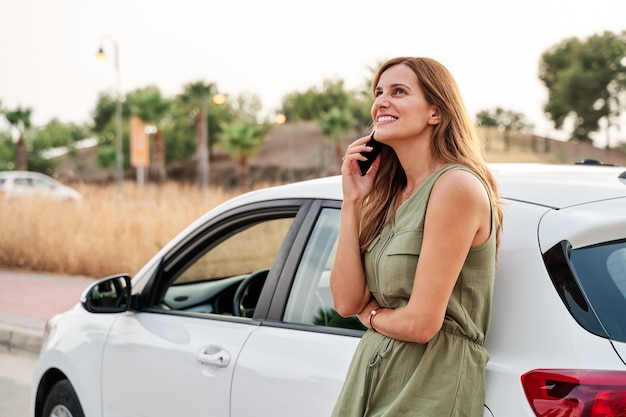Young pretty woman standing leaning against her car while talking on her smartphone.