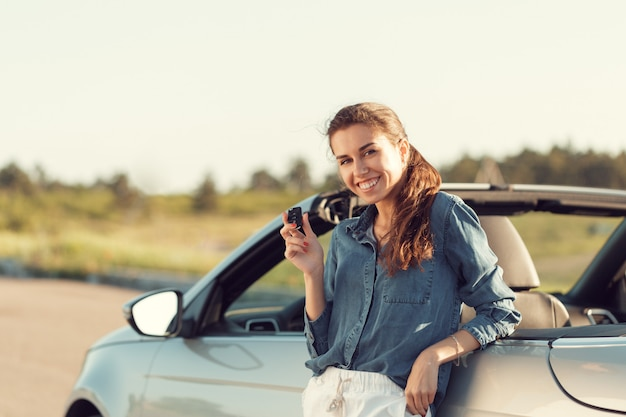 Young pretty woman standing near convertible with keys in hand