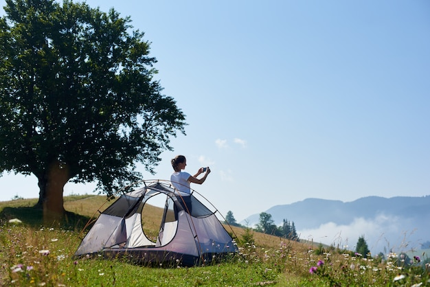Young pretty woman standing on steep grassy hill at small tourist tent and big tree and taking picture of beautiful foggy mountains covered with forest under clear blue sky on bright summer morning.