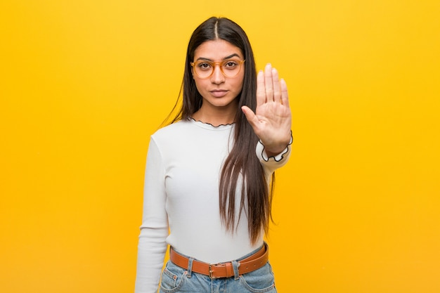 Молодая красивая женщина, стоя с вытянутой рукой, показывая знак остановки, предотвращая вас