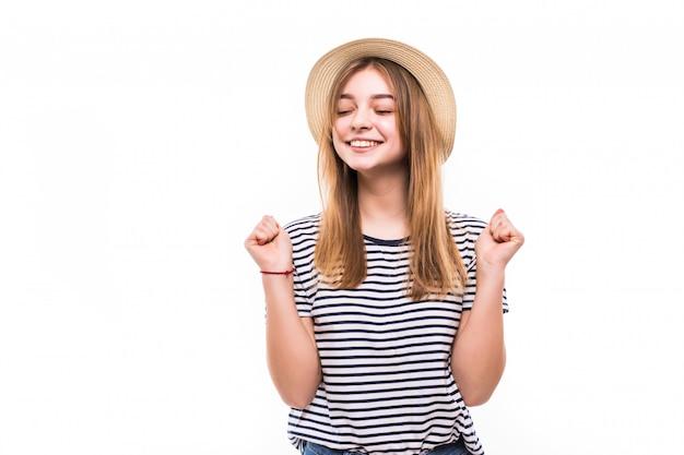 Giovane donna graziosa nel gesto di vittoria del cappello di paglia isolato sulla parete bianca