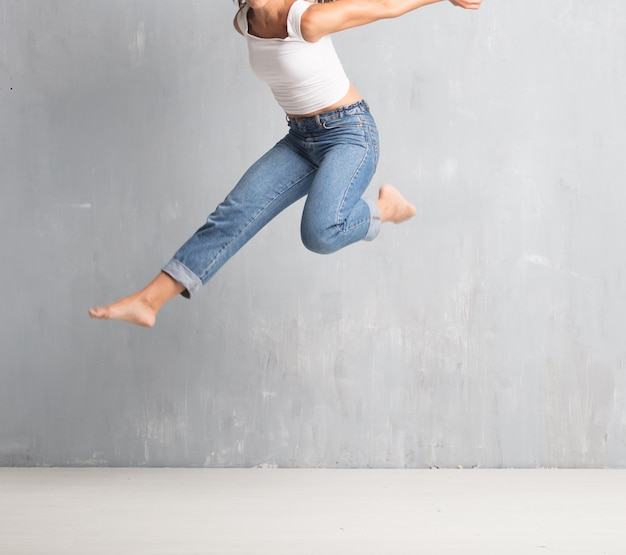 Young pretty woman street dancer jumping against grunge wall bac