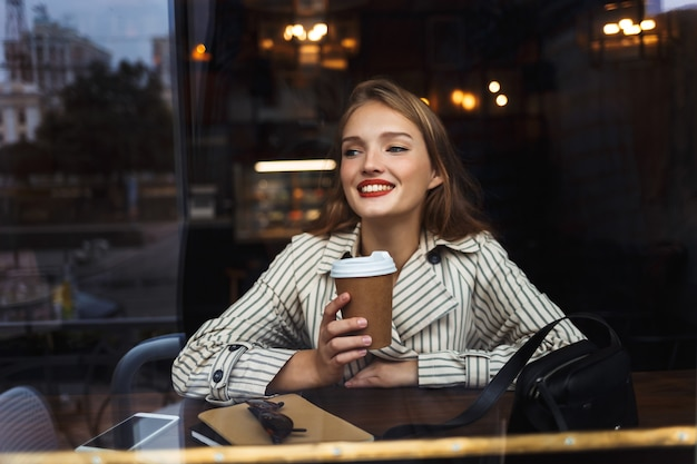 Young pretty woman in striped trench coat holding cup to go in hand joyfully