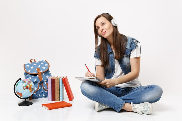 Young pretty woman student in headphones looking up dreaming listen music writing notes on notebook near globe backpack books isolated