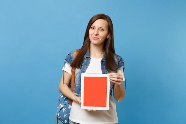 파란색 배경에 격리된 빈 검은색 빈 화면이 있는 태블릿 Pc 컴퓨터를 들고 배낭을 메고 데님 옷을 입은 젊고 예쁜 여학생입니다. 고등학교에서 교육입니다. 광고 공간을 복사합니다. 프리미엄 사진