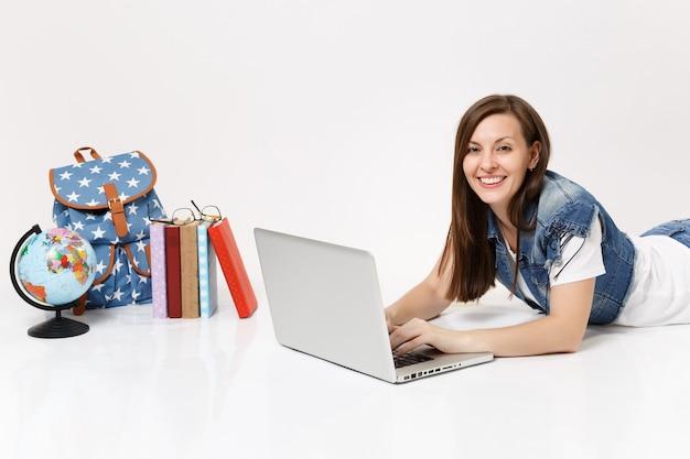 Молодая красивая женщина-студентка в джинсовой одежде работает на портативном компьютере, лежащем рядом с рюкзаком глобуса и школьными учебниками