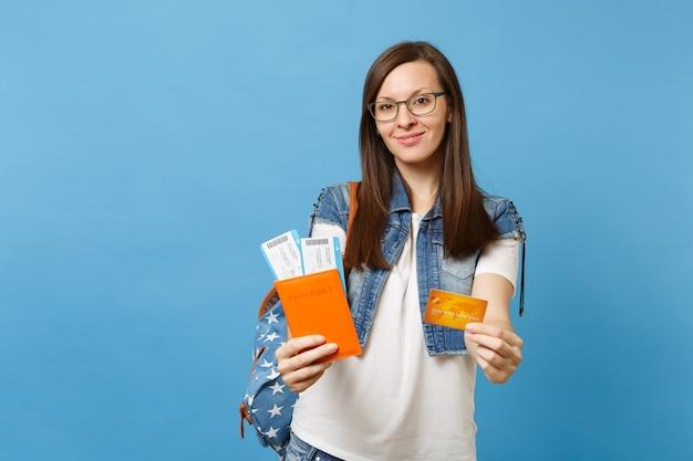 Молодой симпатичный студент женщины в очках с рюкзаком, держащим паспорт, билеты на посадочный талон, кредитную карту, изолированную на синем фоне. обучение в вузе за рубежом. концепция полета авиаперелета.