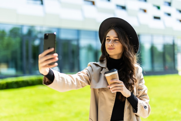 Young pretty woman student wear in coat and hat holding coffee to go take selfie on the phone in the street