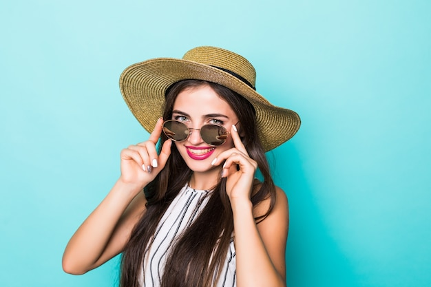 Young pretty woman in summer clothes hat and sunglasses on turquoise background