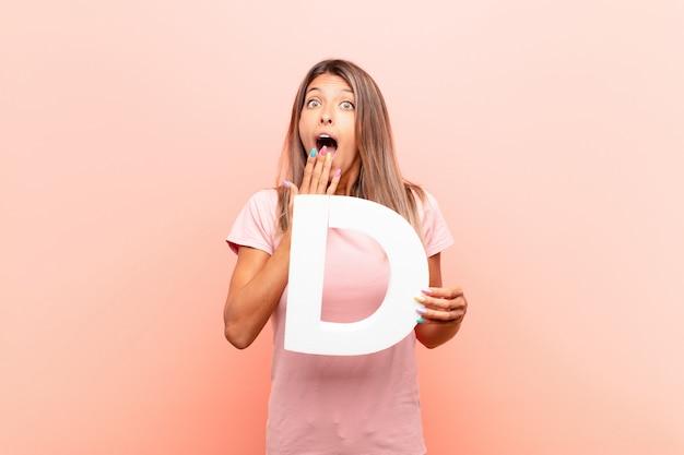 Молодая симпатичная женщина удивлена, потрясена, поражена, держа букву d в алфавите, чтобы образовать слово или предложение.
