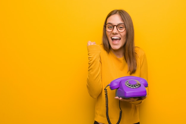 Young pretty woman surprised and shocked she is holding a vintage telephone.