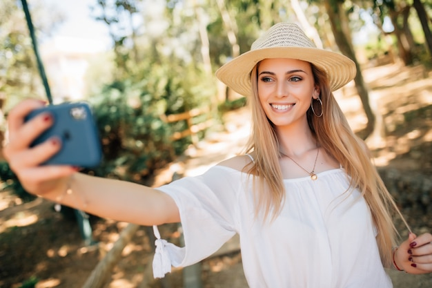 Young pretty woman taking a selfie in a stylish summer hat in a park.