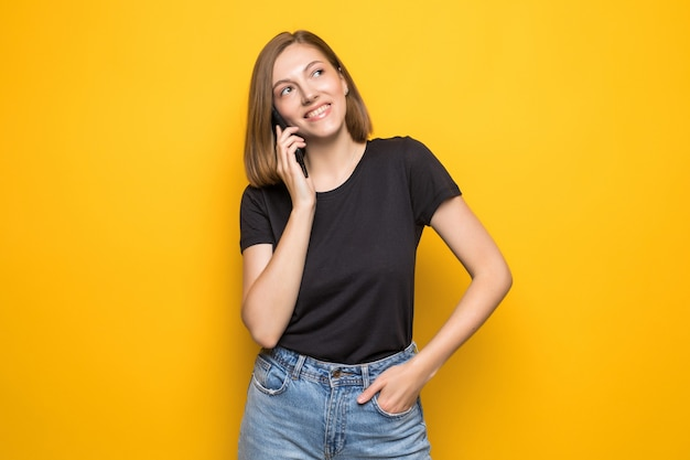 Young pretty woman talking on cell phone over yellow wall