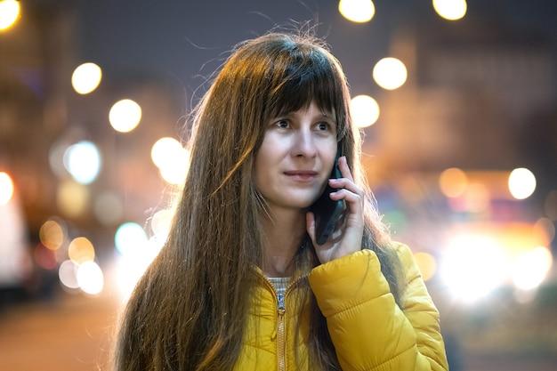 야외 밤에 도시 거리에 서 있는 그녀의 휴대 전화에 얘기 하는 젊은 예쁜 여자.