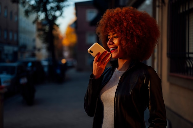 日没時に電話で話している若いきれいな女性
