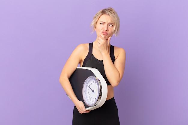 考えて、疑わしくて混乱している若いきれいな女性。ダイエットコンセプト