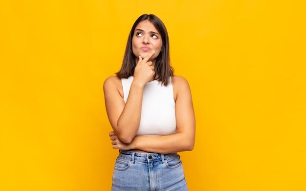 若いきれいな女性が考え、疑わしくて混乱し、さまざまな選択肢があり、どの決定を下すか疑問に思っています