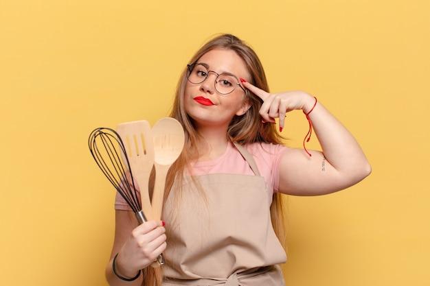 Молодая красивая женщина. думающий или сомневающийся выражение шеф-повар кулинария концепция