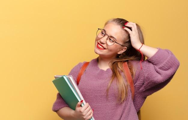 Молодая красивая женщина. думающее или сомневающееся выражение. студенческая концепция