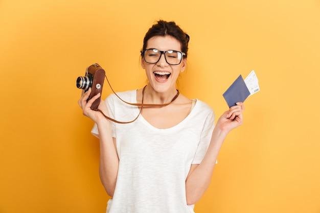 Молодая красивая женщина турист держит паспорт с билетами и камерой