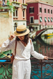 Young pretty woman traveler standing at venice bridge cross canal gondolas in water