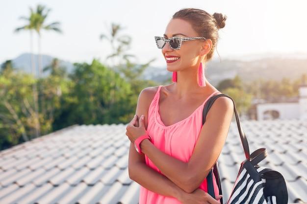 Giovane donna graziosa che viaggia con lo zaino in vacanza estiva nel paese tropicale, sorridente, emozione felice, guardando da parte, vestito alla moda hipster, occhiali da sole