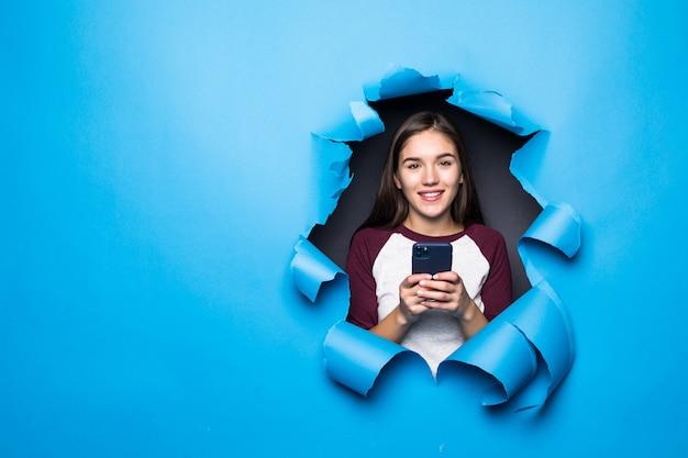 젊은 예쁜 여자 입력 및 종이 벽에 파란색 구멍을 통해 보면서 전화를 사용합니다.