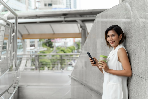 Young pretty woman use smartphone in public