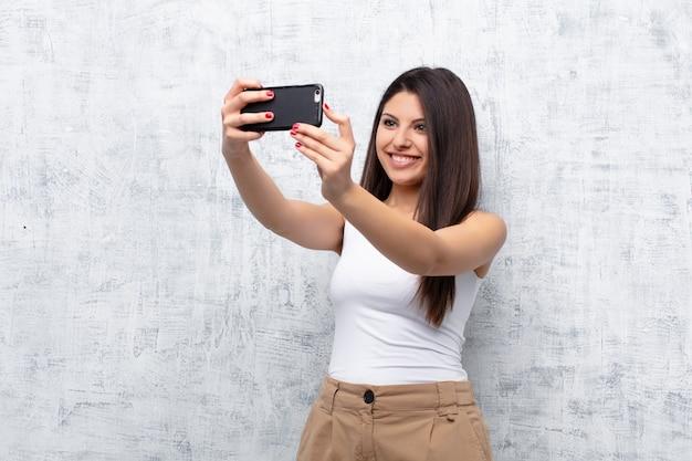 グランジの壁にスマートフォンを使用して若いきれいな女性