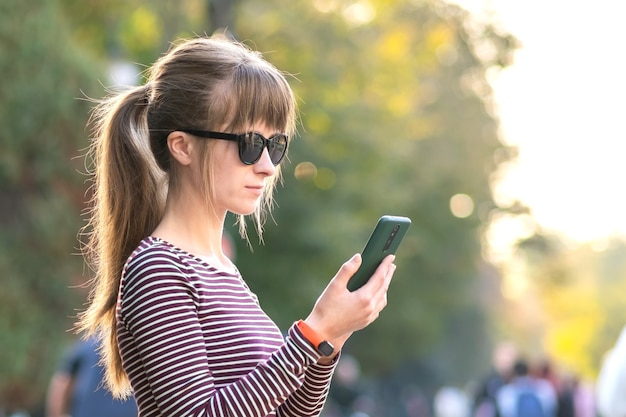 Молодая красивая женщина с помощью своего мобильного телефона в теплый летний день на открытом воздухе.