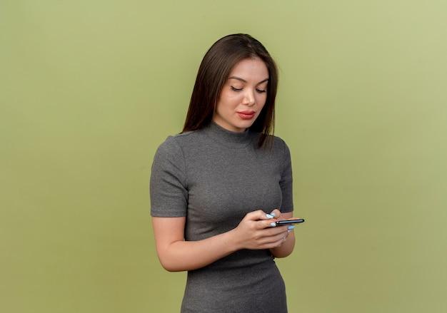 Молодая красивая женщина с помощью мобильного телефона, изолированного на оливково-зеленом фоне с копией пространства