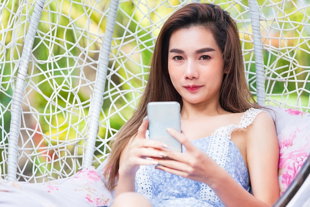 Young pretty woman using smartphone in swing
