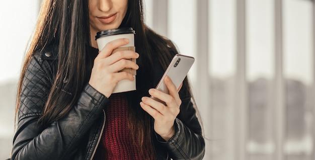 一杯のコーヒーと友達と電話で話している若いきれいな女性