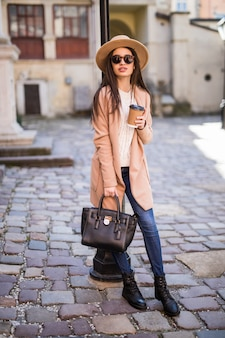 Young pretty woman walking along the street with handbag and cup of coffee.