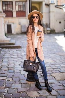 ハンドバッグと一杯のコーヒーが付いている通りに沿って歩く若いきれいな女性。