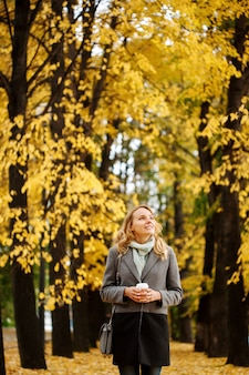 Young pretty woman walking in the autumn park with cup of coffee