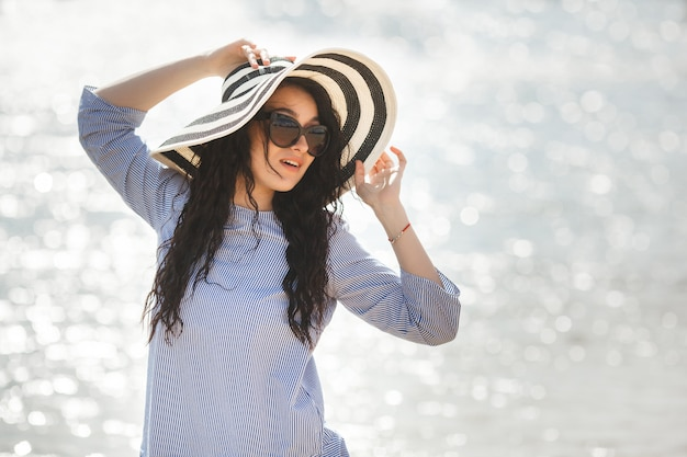 Young pretty woman walking on a beach. attractive adult girl near the water relaxing. beautiful woman on the sea
