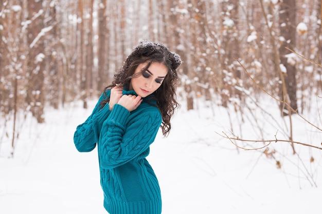 雪の公園を歩く若いきれいな女性