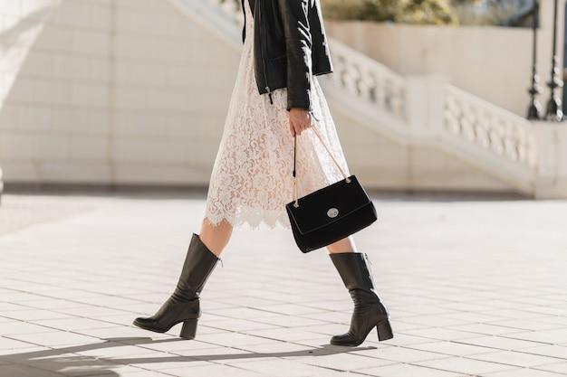 검은 가죽 재킷과 흰색 레이스 드레스, 봄 가을 스타일, 따뜻하고 화창한 날씨, 낭만적 인 표정을 입고 지갑을 들고 유행 복장으로 거리를 걷는 젊은 예쁜 여자