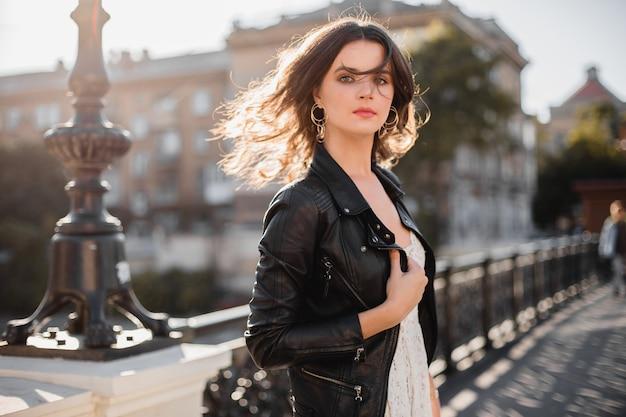 ファッショナブルな服装で通りを歩いて、財布を持って、黒い革のジャケットと白いレースのドレスを着て、春秋のスタイルの若いきれいな女性