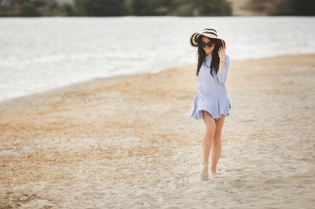 ビーチの上を歩く若いきれいな女性。リラックスできる水の近くの魅力的な大人の女の子。海の上の美しい女性