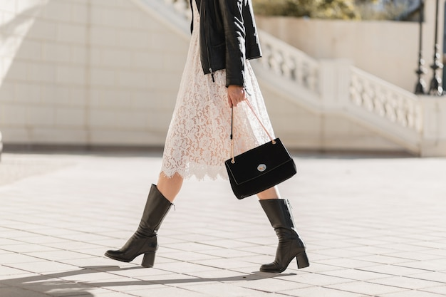 Young pretty woman walking in street in fashionable outfit, holding purse, wearing black leather jacket and white lace dress, spring autumn style, warm sunny weather, romantic look