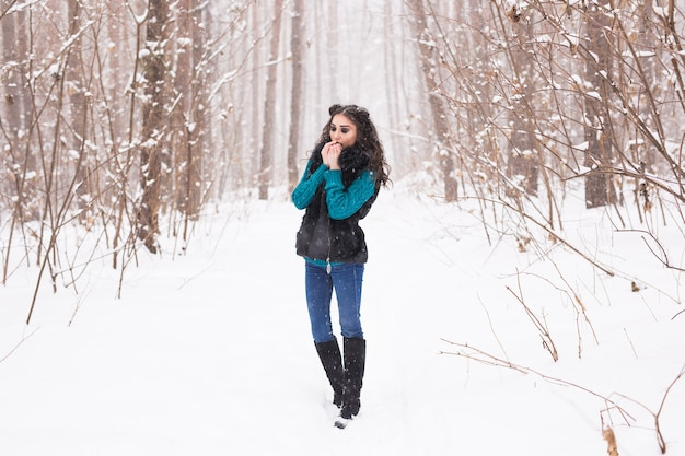 Young pretty woman walking in the winter snowy park at sunny day.