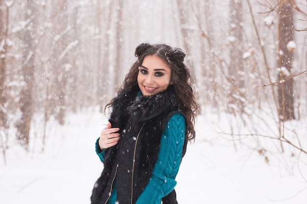 Young pretty woman walking in the winter snowy park at sunny day