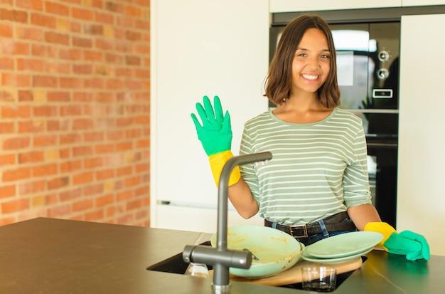Молодая симпатичная женщина моет посуду, улыбается и выглядит дружелюбно, показывает номер пять или пятое с рукой вперед, отсчитывая