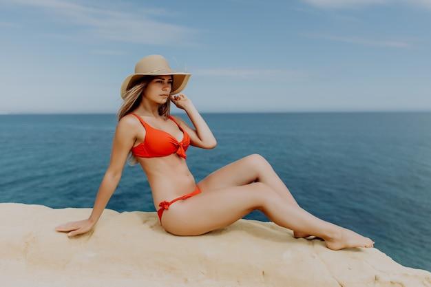 젊은 예쁜 여자는 바위에 앉아 빨간 섹시한 비키니를 착용
