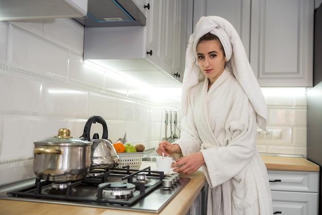バスローブを着てコーヒーを飲む若いきれいな女性は、キッチンでリラックス